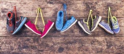 Obraz Buty sportowe powiesić na gwoździu na drewnianym tle ogrodzenia