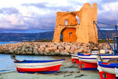 Calabria, Italy. Picturesque old harbour with tradtional fishing boats and saracen tower in Briatico village.
