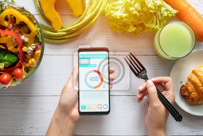 Obraz Calories counting , diet , food control and weight loss concept. woman using Calorie counter application on her smartphone at dining table with salad, fruit juice, bread and vegetable