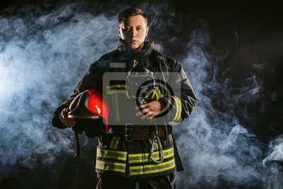 Obraz caucasian modern hero fireman in uniform don't afraid of danger, looking for people to save, using ropes, hammers and other equipment need for protection