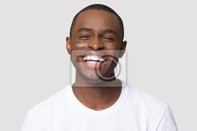 Obraz Cheerful happy african millennial man laughing looking at camera isolated on studio blank background, funny young black guy with healthy teeth beaming orthodontic white wide smile head shot portrait