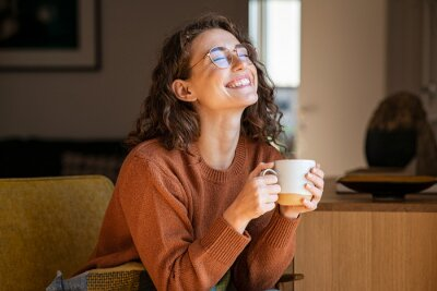 Obraz Cheerful woman enjoying coffee cup in a winter afternoon