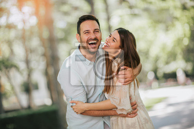 Obraz Cheerful young couple having fun and laughing together outdoors