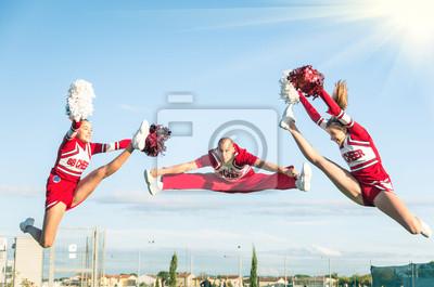 Obraz Cheerleaders zespół wykonując skok z męskiego trenera