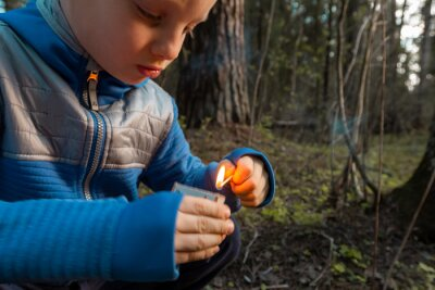 Obraz Child lighting match. The fire in the hands of a children. A little boy plays with flame. Danger of woodfire