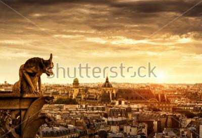 Obraz Chimera lub gargulec w katedrze Notre Dame de Paris z widokiem na Paryż o zachodzie słońca, Francja. Panorama Paryża ze złym posągiem w słońcu. Piękny słoneczny widok na Paryż pod dramatycznym niebem.