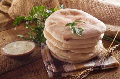 Obraz chleb pita i sosem tzatziki na drewnianym stole.