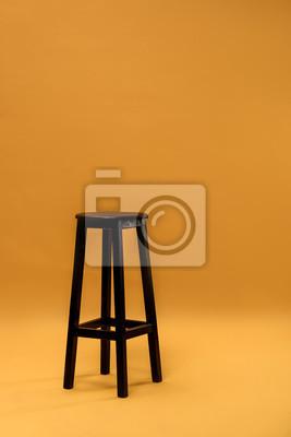 Ciemna drewniana prętowa stolec na pomarańczowym tle