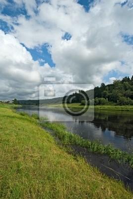 ciemnoniebieskie wodach rzeki, zielona trawa i błękitne niebo