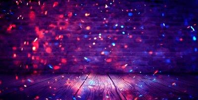 Obraz Ciemny pokój w piwnicy, pusty stary mur, iskry ognia i światła na ścianach i drewnianej podłodze. Ciemne tło z dymem i jasnymi refleksami. neony na ścianie, widok nocny.