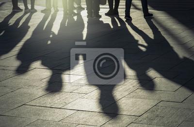 Obraz Cienie i sylwetki ludzi w mieście podczas zachodu słońca