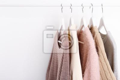 Obraz Ciepłe, dzianinowe, jesienne, zimowe ubrania wiszące na stojaku, trendująca koncepcja, pastelowe kolory