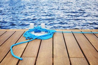 Cleat z niebieską liną na drewnianym molo, bezpieczna koncepcja podróży.