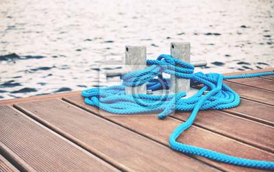 Cleat z niebieską liną na drewnianym molo, koncepcją podróży lub bezpieczeństwa, zastosowano tonację kolorową.