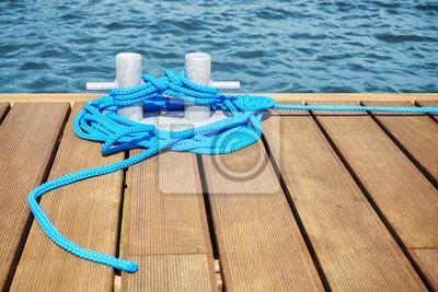 Cleat z niebieską liną na drewnianym molo, płytkiej głębi ostrości.