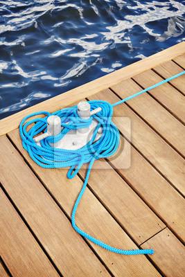 Cleat z niebieską liną na drewnianym molo, podróży lub koncepcji bezpieczeństwa.