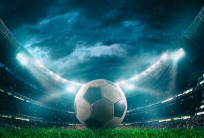Obraz Close up of a soccer ball in the center of the stadium illuminated by the headlights