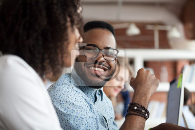 Obraz Close up of smiling African American employee look at female colleague chatting in office, happy black male worker talk with woman coworker, having casual conversation at workplace, have fun