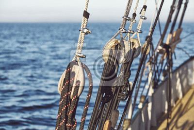 Close up picture of old wooden pulleys on a sailing ship, selective focus.