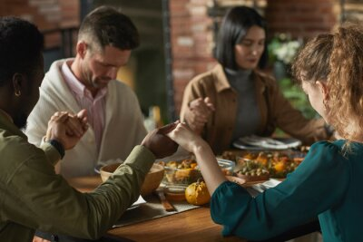 Obraz Close up portrait of multi-ethnic group of elegant young people praying and holding hands while sitting at dinner table during Thanksgiving celebration, copy space