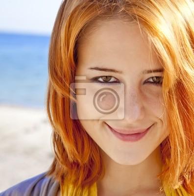 Close-up portret rudowłosej dziewczyny na wolnym powietrzu z niebieskim morzu w