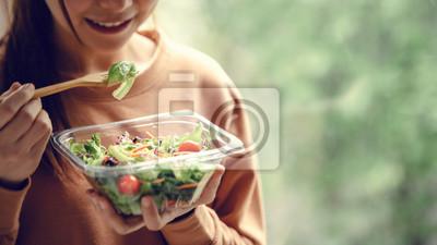 Obraz Closeup woman eating healthy food salad, focus on salad and fork.
