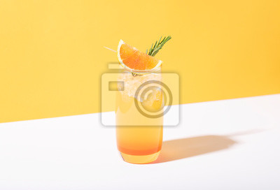 Obraz Cold and refreshing orange punch cocktail with orange slice on yellow background. summer drink.