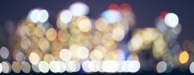 Color toned blurred city lights at night, urban abstract background.