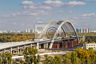 Combined car and subway bridge under construction. Mounting of steel arch. Unfinished Podilskiy bridge (Podilsko-Voskresenskiy bridge). Kiev, Ukraine. Kyiv, Ukraine.