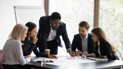 Obraz Confident african American male boss work cooperate with diverse team at office briefing, focused biracial businessman head meeting, collaborate discuss business ideas with colleagues at meeting