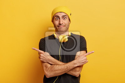 Obraz Confused European man crosses hands over chest, points at different sides, stares surprisingly at camera, makes choice between two options, wears yellow hat and black t shirt, uses headphones