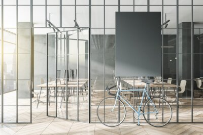 Obraz Contemporary glass partition and bike in stylish coworking office interior with empty black mock up poster and city view and daylight. 3D Rendering.