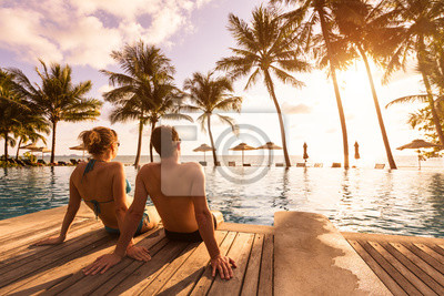Obraz Couple enjoying beach vacation holidays at tropical resort with swimming pool and coconut palm trees near the coast with beautiful landscape at sunset, honeymoon destination