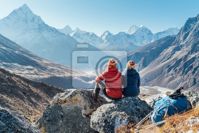 Obraz Couple resting on the Everest Base Camp trekking route near Dughla 4620m. Backpackers left Backpacks and trekking poles and enjoying valley view with Ama Dablam 6812m peak and Tobuche 6495m