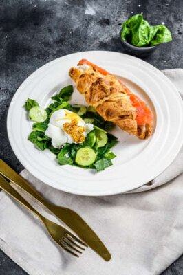 Obraz Croissant sandwich with salted salmon served with fresh salad leaves spinach, egg and vegetables.
