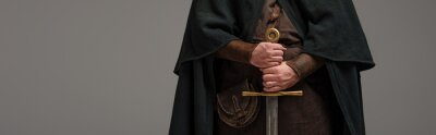 Obraz cropped view of medieval Scottish knight in mantel with sword in hands on grey background, panoramic shot