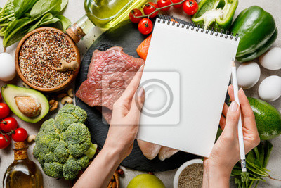 Obraz cropped view of woman holding empty notebook above food for ketogenic diet menu