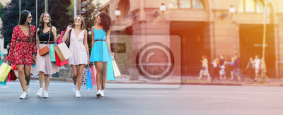 Obraz Crossing roads. Full-length photo of four beautiful women walking along the city street in sophisticated dresses and carrying shopping bags, laughing and chatting to each other.