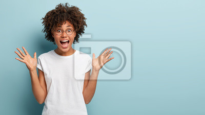 Obraz Curly optimistic woman raises palms from joy, happy to receive awesome present from someone, shouts loudly, dressed in casual white t shirt, isolated on blue background. Excited Afro female yells