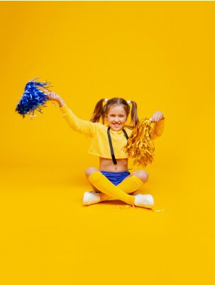 Obraz cute cheerleader girl in a yellow tank top and blue shorts sits with pompons in her hands