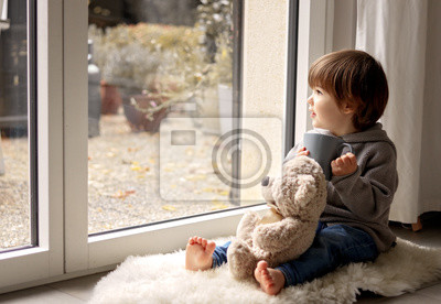 Obraz Cute little toddler boy sitting at window with cup of warm tea with his soft teddy bear toy looking out thoughtfully at chilly autumn weather. Cozy home. Fall melancholy concept. Seasonal mood
