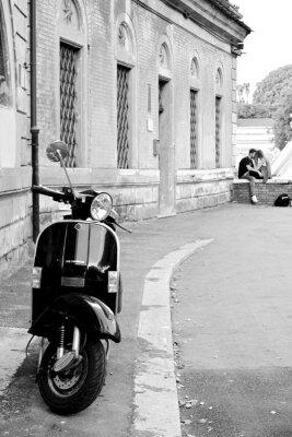 Obraz Czarno-białe zdjęcie z charakterystycznym skuter z młodej pary w tle.