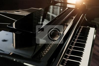 Obraz Czarny błyszczący fortepian z białą klawiaturą w ciemnym odcieniu