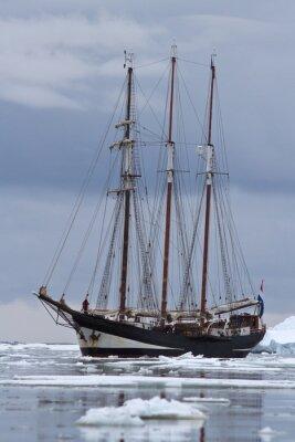 Obraz Czarny statek turystyczny pływający po wodach Antarktyki zatkane lodem