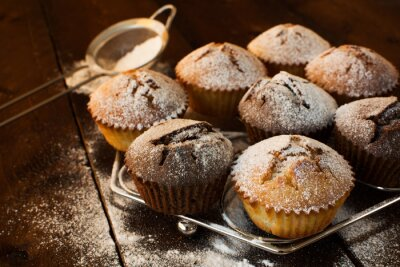 Obraz Czekolady i wanilii babeczki, cukru pudru, sita do pieczenia na ciemnym tle drewniane, selektywne focus