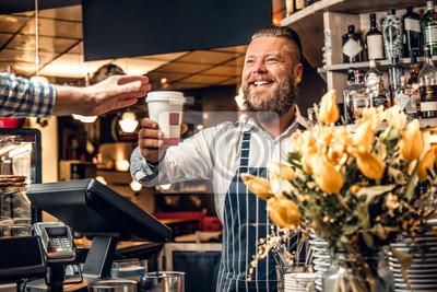 Obraz Człowiek sprzedający kawę konsumentowi w kawiarni.