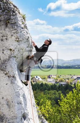 Człowiek wspinający naturalne skaliste ściany z pięknym widokiem.