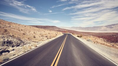 Desert road in Death Valley, color toning applied, USA.