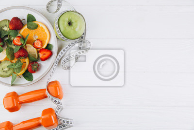 Obraz Diet plan, menu or program, tape measure, water, dumbbells and diet food of fresh fruits on white background, weight loss and detox concept, top view