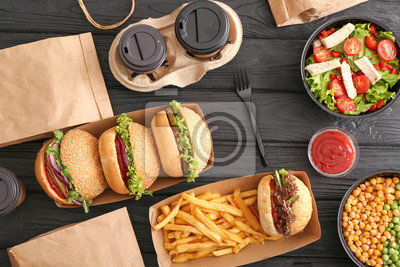 Obraz Different tasty food from delivery service on wooden background